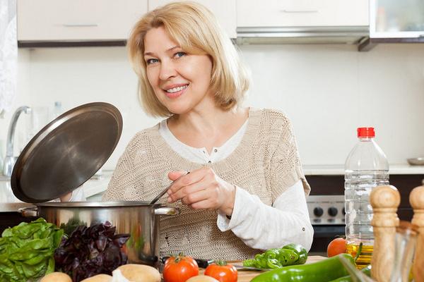 Женщина варит суп